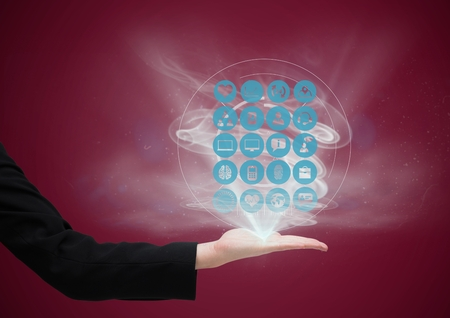 Digital composite of hand with application icons coming up from it. dark red background