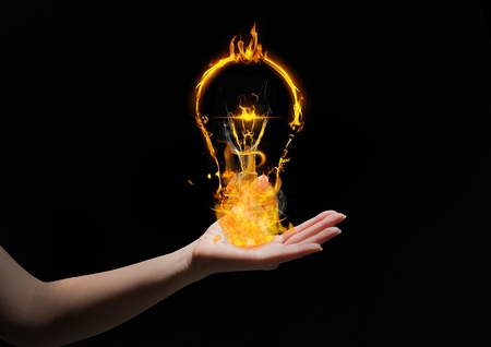 Digital composite of hand with light fire icons over. Black background