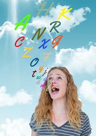 Digital composite of young  woman shouting with colour letters coming up from mouth Stock Photo