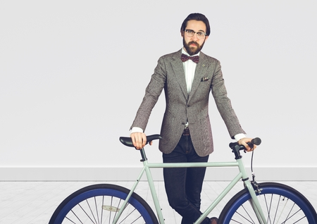 smart boy: Digital composite of Millennial man in suit with bike against white wall Stock Photo