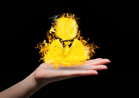 Digital composite of hand with contact  fire icon over. Black background Stock Photo
