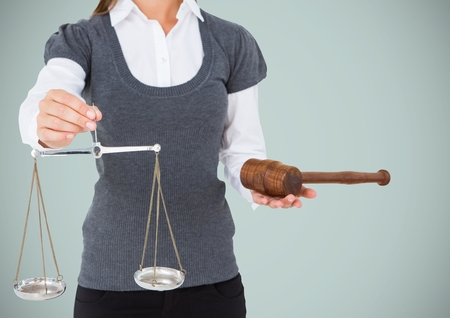 Digital composite of Female judge mid section with scales and gavel against grey background