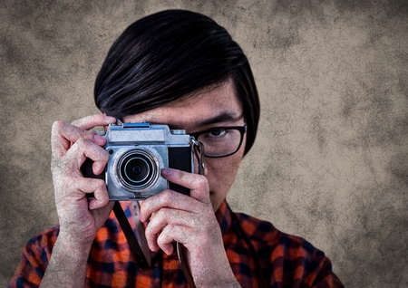 Digital composite of Close up of millennial man with camera against brown background with grunge overlay Stock Photo