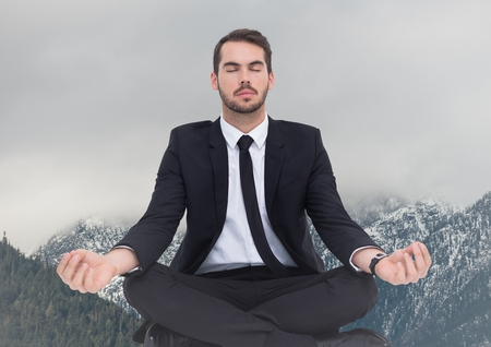 non: Digital composite of Business man meditating  against snowy mountains