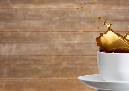 high: Digital composite of White cup with coffee splashing against blurry wood panel