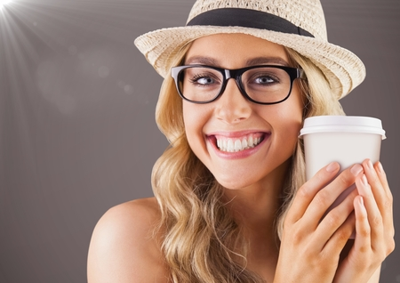 Digital composite of Close up of millennial woman smiling with coffee and flare against brown background Stock Photo