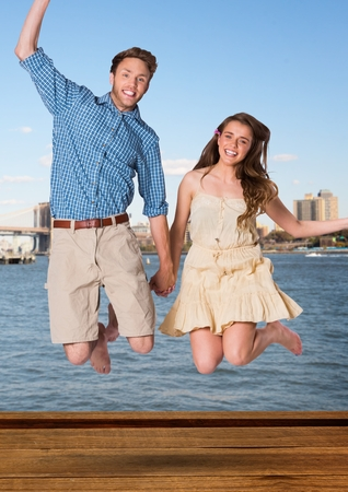 Digital composite of Couple jumping in air against water and skyline