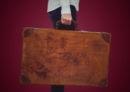 Digital composite of Millennial woman lower body with suitcase against maroon background