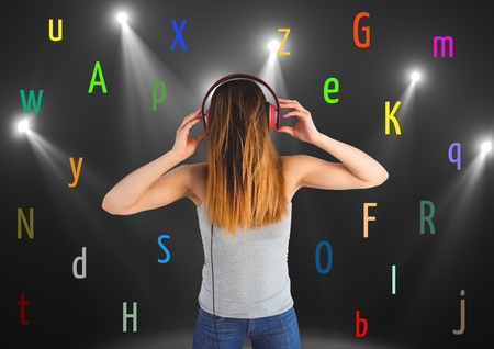 Digital composite of young woman listening music with colour letters around. Black back