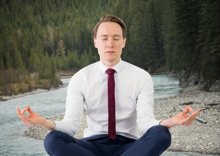 Digital composite of Business man meditating against river