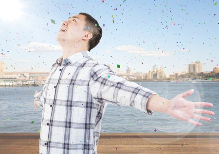 innumerable: Digital composite of Man with arms outstretched against water and skyline with flare and confetti