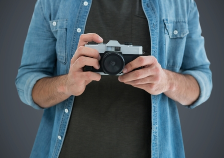 gray texture: Digital composite of Millennial man mid section with camera against grey background