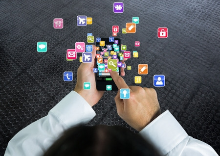 Digital composite of Man with phone on  hands and applications icons coming up from it