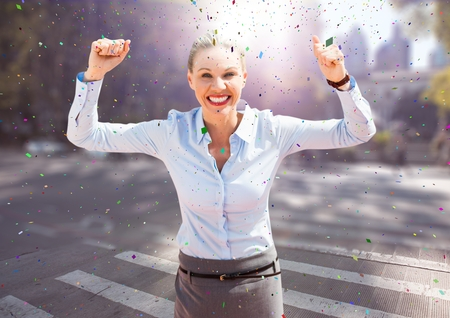 Digital composite of Business woman hands in air on blurry street with flares and confetti Stock Photo