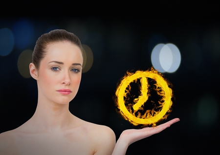 Digital composite of woman with hand up with clock fire icon over. Dark bokeh background.