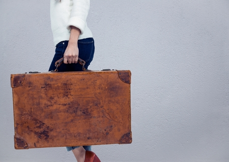 Digital composite of Millennial woman lower body with briefcase against grey wall Stock Photo