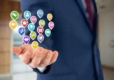 non: Digital composite of businessman with hand spread of  with application icons over. office blurred background