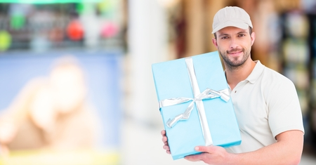 Digital composite of Delivery man with blue gift against blurry shopping center Stock Photo