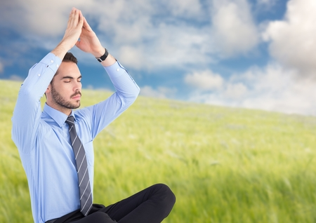 Digital composite of Business man meditating against blurry meadow