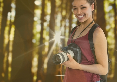 Digital composite of young happy photographer in the forest. With flares and bokeh overlap