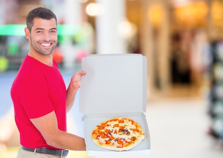 shopping binge: Digital composite of Delivery man with pizza against blurry shopping centre Stock Photo