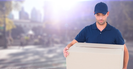 Digital composite of Delivery man with box against blurry street with flare Stock Photo