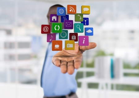 Digital composite of businessman (blurred) with hand spread of with application icons over. Blurred office background
