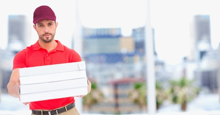 Digital composite of Delivery man with pizzas against blurry buildings Stock Photo