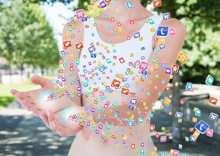 Digital composite of hands with application icons coming up form it. Blurred park background Stock Photo