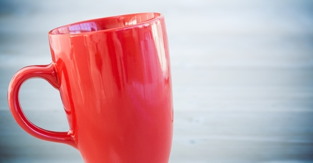 Digital composite of Red cup against blurry blue wood panel