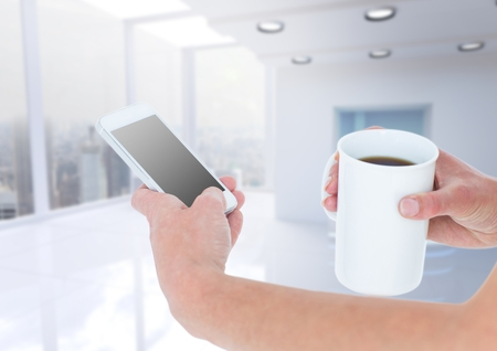 innumerable: Digital composite of Hands with coffee and phone against blurry white office Stock Photo