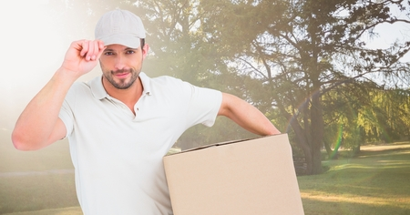 Digital composite of Delivery man with box against blurry park with flares Фото со стока
