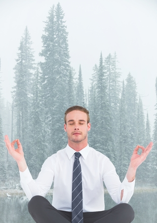 non: Digital composite of Business man meditating against misty river and trees