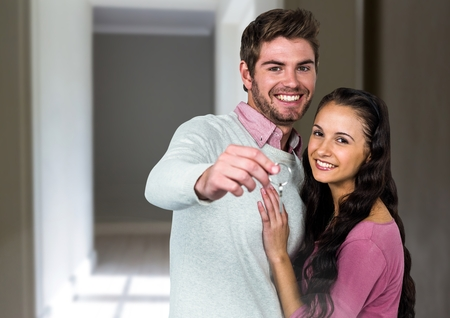 guy standing: Digital composite of Couple Holding Keys at home