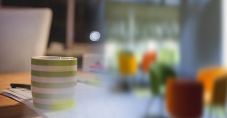 Digital composite of Green and white coffee cup on desk and blurry office transition Stock Photo