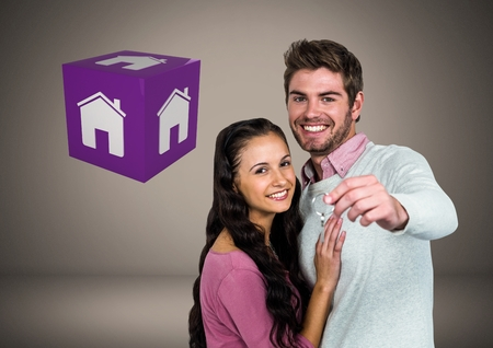 Digital composite of Couple Holding key with house icon cube in front of vignette