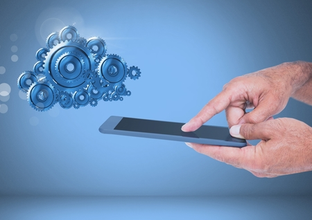 Digital composite of Touching smart screen with cog gears cloud Stock Photo