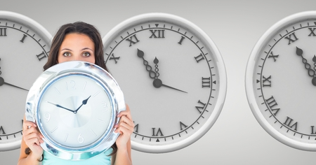 organisational: Digital composite of Woman holding a clock against background with clocks Stock Photo