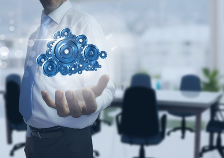 Digital composite of Businessman with Open hand with cog gears in office