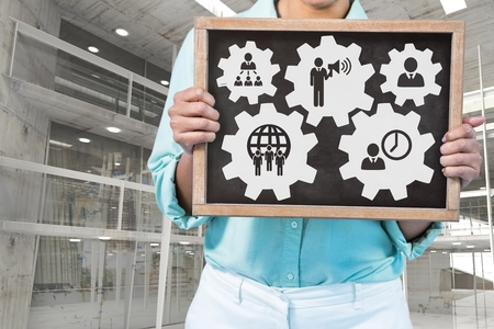 organisational: Digital composite of Business woman holding a blackboard with people in cogs graphics against office background