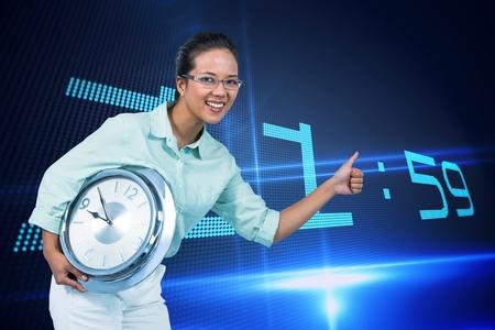 Digitale composiet van Gelukkige zakenvrouw die een klok tegen de achtergrond met de klok houdt Stockfoto