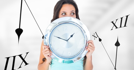 Digital composite of Woman holding a clock against background with clocks Stock Photo