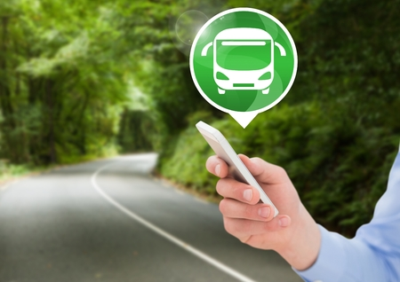 Digital composite of Hand holding phone with bus icon on road