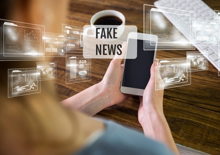 Digital composite of Holding phone with Fake news text and interface Stock Photo - 86518719