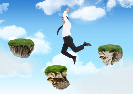 Digital composite of Businessman jumping between steps of floating rock platforms in sky