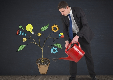 Digital composite of Man holding watering can and Drawing of Business graphics on plant branches on wall Stock Photo