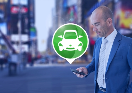 Digital composite of Man holding phone with car icon in city Stock Photo