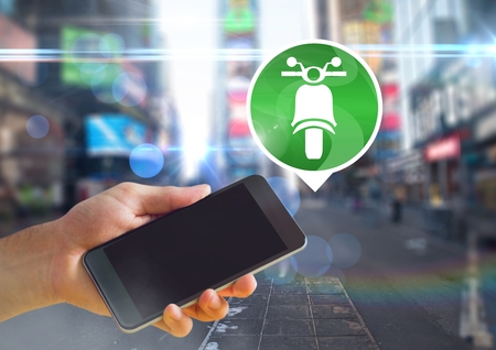 Digital composite of Hand holding phone with motorbike icon in city Stock Photo