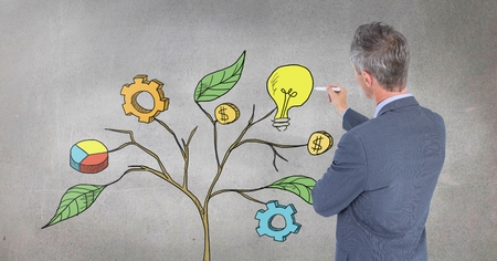 Digital composite of Man holding pen and Drawing of Business graphics on plant branches on wall Stock Photo