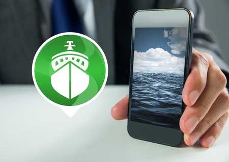Digital composite of Hand holding phone with ship icon with sea